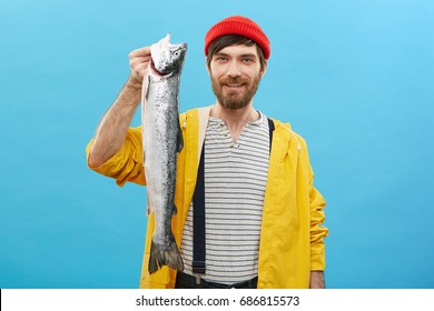 Happy fisherman with blue eyes and thick beard wearing red casual hat and yellow anorak holding in hand very big long fish which he catched on sea last night rejoicing his successful fishing trip