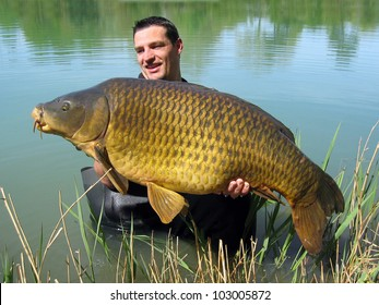 Happy  fisherman holding a beautiful common carp