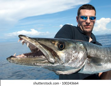 Happy  fisherman holding a giant barracuda - Close up on barracuda teeth