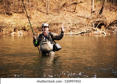 Happy fisherman holding a grayling caught from the river