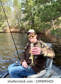 Happy fisherman holding a Walleye while sitting in a boat with lake and shoreline in the background