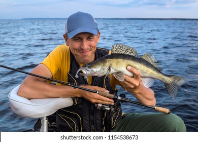 Happy fisherman with zander walleye fish trophy at the boat with fishing tackles