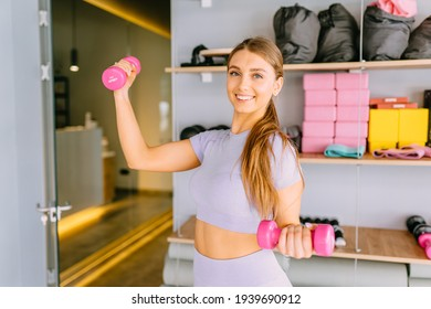 Happy fit caucasian woman doing an exercise with dumbbells over modern studio interior background. Smiling girl. Fitness Workout. Healthy lifestyle concept.