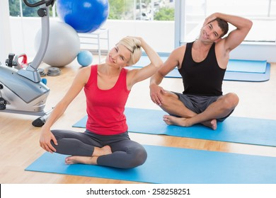 Happy fit couple working on exercise mat in fitness studio