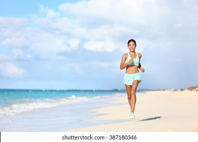 Happy fit female runner running on sand during summer travel vacation on tropical beach. Asian woman jogging doing cardio training exercising for weight loss. Happiness and wellbeing concepts.