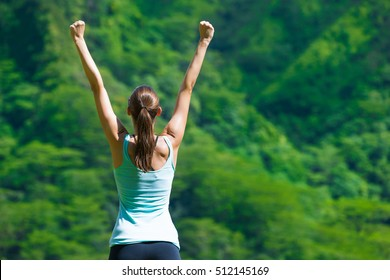 Happy fit girl with her arms in the air celebrating. Healthy and active lifestyle concept.