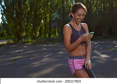 happy fit girl posing in the park with her phone and thermo cup