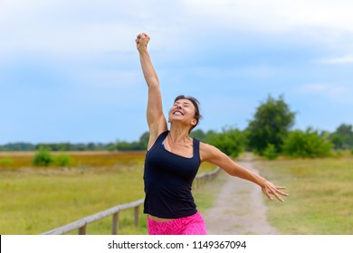 Happy fit middle aged woman cheering and celebrating as she walks along a rural lane  after working out jogging in a close up view