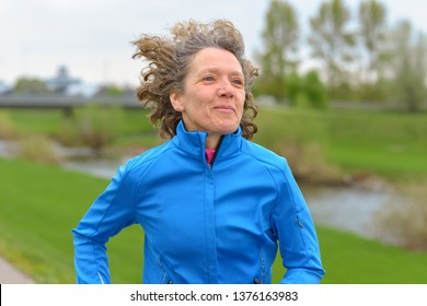 Happy fit middle-aged woman out jogging along a rural road in a close up portrait smiling as she passes the camera