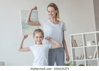 happy fit mother and daughter showing biceps muscles