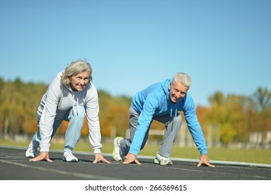 Happy fit senior couple jogging at stadium