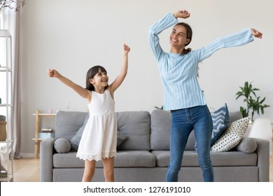 Happy fit sporty mother or baby sitter and funny active child daughter having fun dancing together at home, smiling mom and kid girl enjoy moving to music raising hands standing in living room