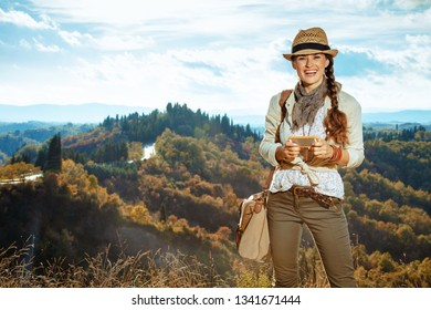 happy fit tourist woman in hiking clothes with bag and smartphone communicating in social media on Tuscany summer hike.
