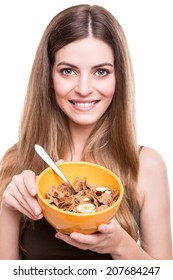 Happy fit woman eating cereals with milk bowl