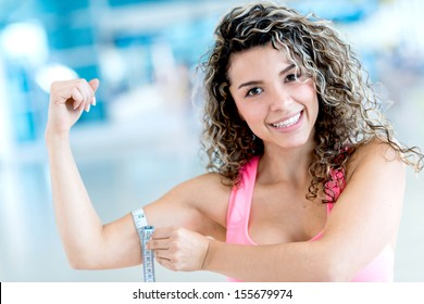 Happy fit woman measuring her arm at the gym