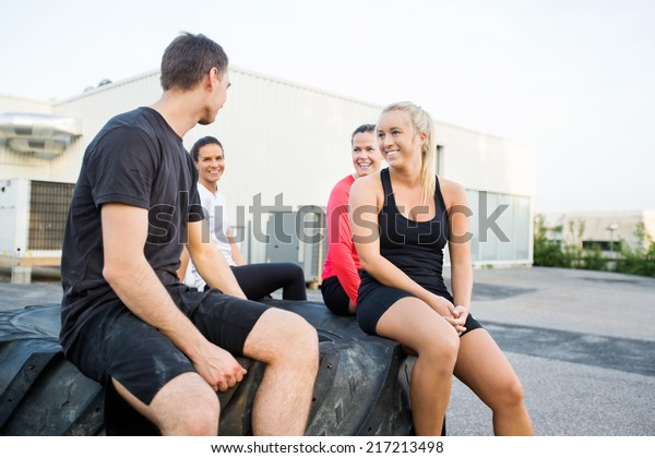 Happy fit young friends relaxing on tire after workout outdoors