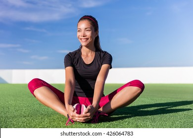 Happy fitness Asian woman butterfly stretching legs in outdoor summer park. Athlete girl doing stretch floor exercises for glutes and inner thigh, groin and hips after running cardio workout.