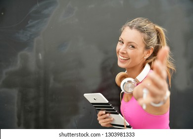 Happy fitness instructor with tablet welcoming you on black background