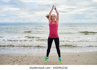 Happy fitness woman doing jumping jacks or star jump exercise at seaside outdoors, copy space. Girl working out on beach at summer morning, full length portrait. Healthy lifestyle concept