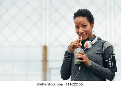 Happy fitness woman drinking detox green smoothie during outdoor city workout rest. Sport nutrition and healthy lifestyle concept.