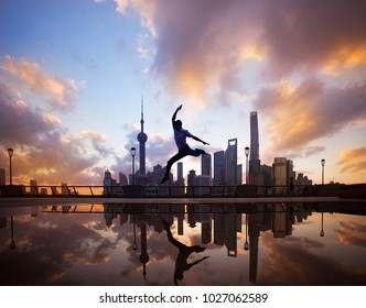 Happy fitness woman jumping of joy and success in Shanghai skyline in goal achievement challenge.action reflected in the water