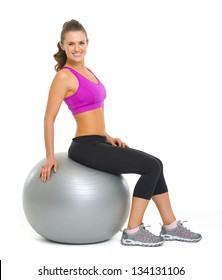 Happy fitness young woman sitting on fitness ball