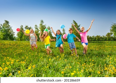Happy five children with balloons run in field