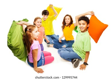 Happy five teen kids, Caucasian, black and Asian, boys and girls ready to start fighting with pillows, laughing and having fun, isolated on white