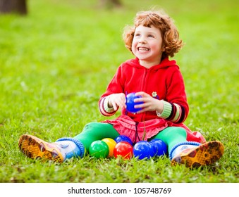 happy five year old girl sitting on the grass and playing with toys on a summer day