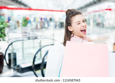 Happy and flirty shopper with paperbags looking and winking at you in the mall