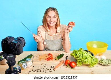 Happy food blogger girl trying out new recipes, recording cooking process, holding raw sliced tomatoe, going to make fresh salad, looking in camera with wide joyful smile.