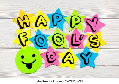 Happy Fool's Day text on colorful sticky notes in the shape of a star on a light wood background.