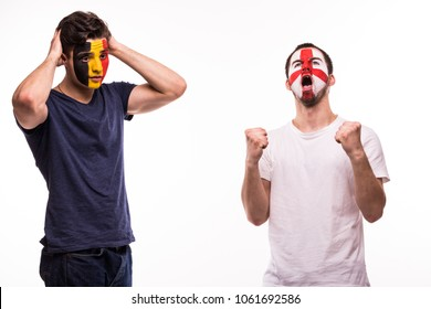 Happy Football fan of England celebrate win over upset football fan of Belgium with painted face isolated on white