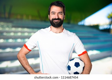 Happy football player holding a soccer ball on a football pitch