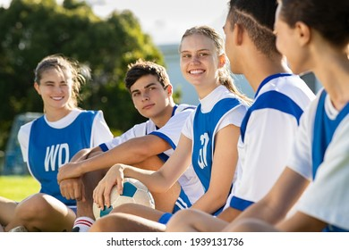 Happy football players sitting on grass on playground field before match. Mixed school soccer players talking during break. Guys and girls teammates sitting in a row for physical education lesson.