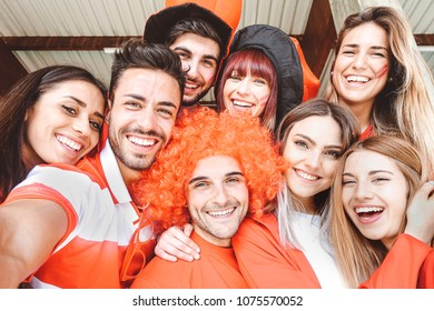 Happy football supporter fans taking a selfie before the world soccer game - Young group of excited friends having fun at stadium - Youth, sport and celebration score concept