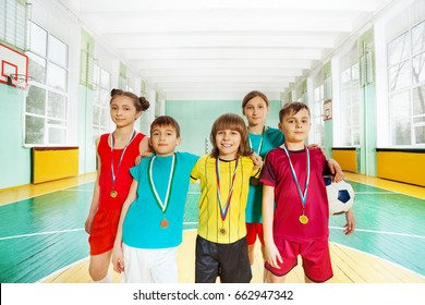 Happy football winners with medals in sports hall