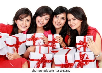 Happy four asian woman with christmas santa hat holding gift boxes on white background