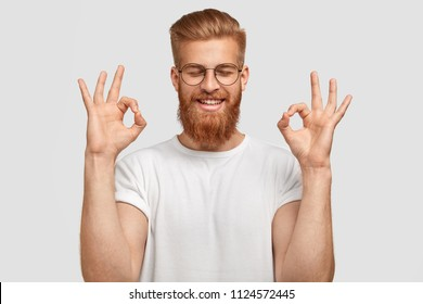Happy foxy young male with satisfied expression, makes okay gesture, closes eyes with happiness, dressed in casual white t shirt, wears casual outfit. Monochrome. Agreement and approval concept