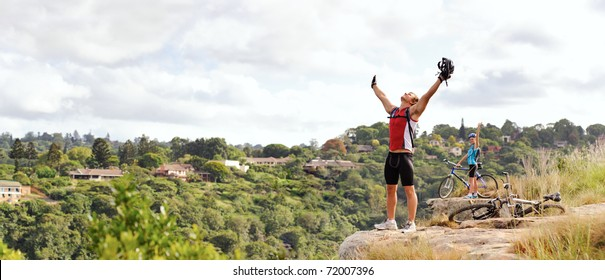 happy free fun man stands victorious on a mountain with arms outstretched and helmet in hand