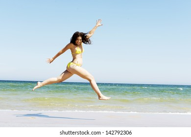 Happy free girl jumping on the beach