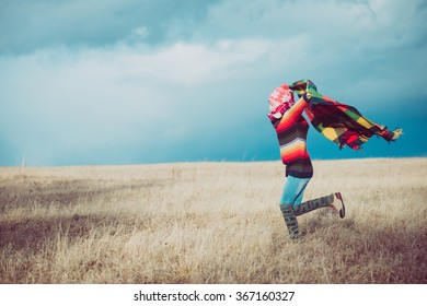 Happy free woman carefree in autumn or winter arms up with a warm blanket enjoying the sun. Beautiful Caucasian girl outdoors.