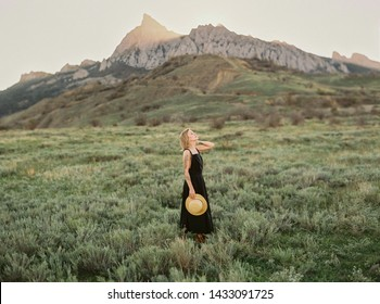 Happy freedom female model in black summer dress and straw hat enjoying mountain nature. Travel holidays vacation outdoors. Freedom and healthy concept.