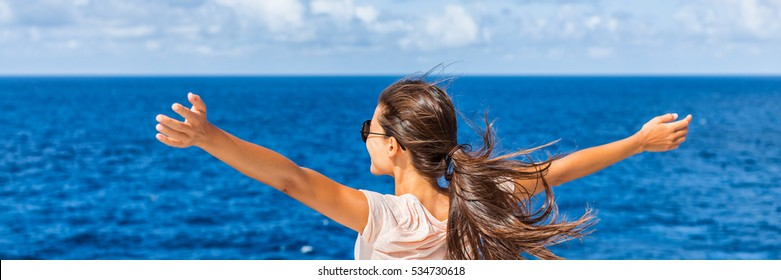 Happy freedom woman with open arms looking at blue sea horizon outdoors. Carefree person living a free life. Panorama horizontal banner crop for success and bliss concept.