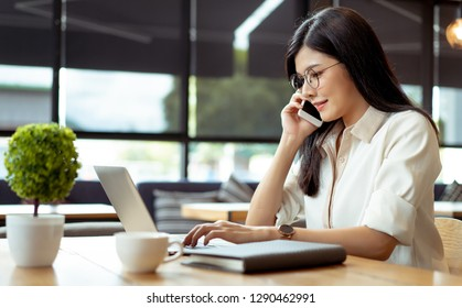 Happy Freelancer asian woman talking customer with smartphone about working job recive order using digital laptop computer on workspace