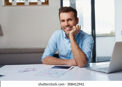 Happy freelancer at homesitting at the desk