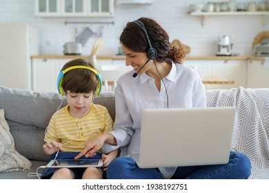 Happy freelancer mother with kid sitting on couch at home office during lockdown work on laptop. Child playing in game at tablet sit on sofa, mom points finger at screen. Family, e-learning concept