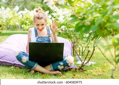 Happy freelancer working in the garden. Writing, surfing in the internet. Young woman waving to the camera during a video call. Distance education, freelance concept.