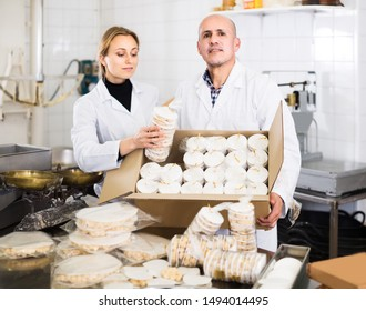 happy french different aged couple standing with box of turron in production workshop