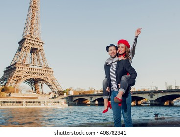 Happy french stereotypical couple having fun on a romantic date under the Eiffel Tower in Paris, France
